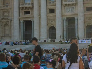 The Pope is sitting between the two columns in front of the center door.